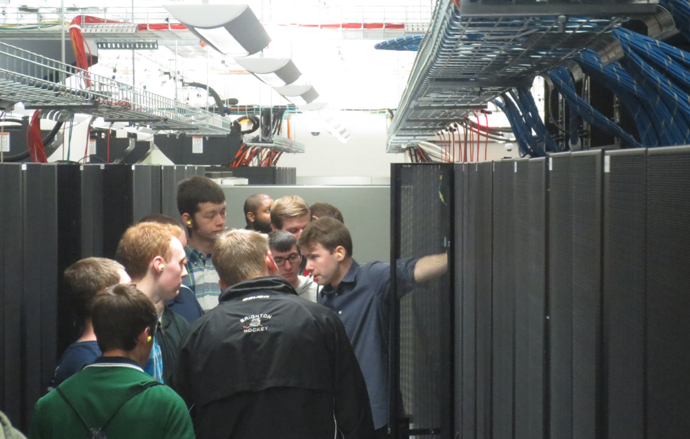 "ARC-TS Systems Programmer Dan Barker, right, leads a tour of Pinckney High School students through the Michigan Academic Computing Center (MACC) in the spring of 2016. The students were from Cyndi Millns' Computer Networking and Security class. ARC-TS Associate Director Brock Palen had spoken to the class earlier in the school year. ""I wanted them to see all the different possibilities available in the area,"" Millns said. ""Hopefully it will spark an interest in some of the students."""